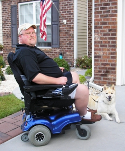 man in motorized wheel chair with dog