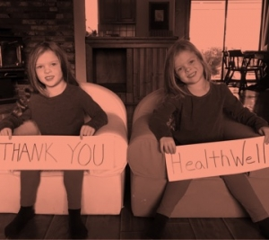 "Two kids sitting down holding signs that say, ""Thank you HealthWell"""